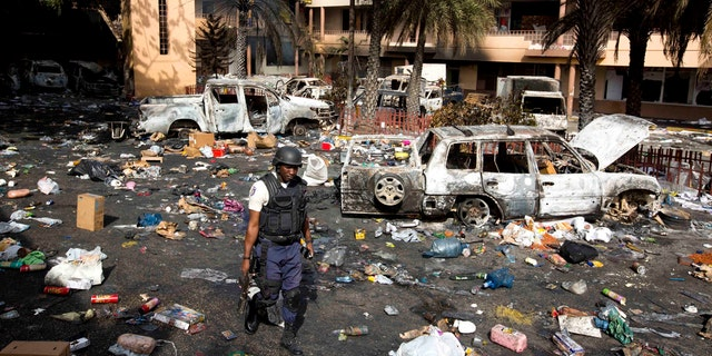 A police officer walks through the parking lot of the Delimart supermarket complex, where vehicles sit charred and looted merchandise lies scattered after two days of protests against a planned hike in fuel prices in Port-au-Prince, Haiti, Sunday, July 8, 2018.