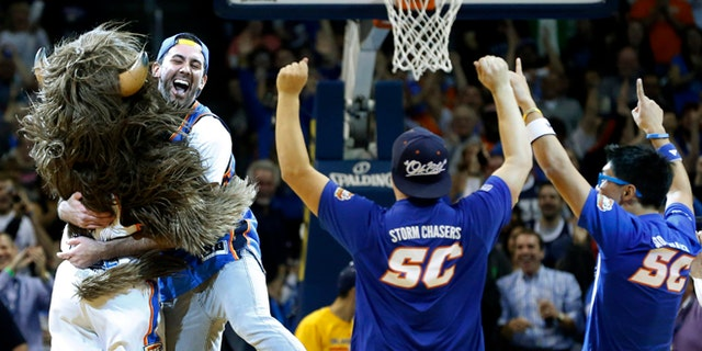 Nov. 18, 2013: Cameron Rodriguez, second from left, celebrates with Thunder mascot Rumble, left, after hitting a half court shot to win $20,000 during a time out of an NBA basketball game between the Oklahoma City Thunder and the Denver Nuggets in Oklahoma City. (AP/Sue Ogrocki)