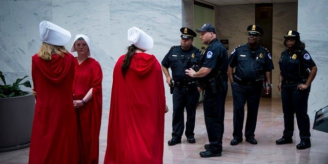 The costumes were likely modeled after the look of the garb from 'The Handmaid's Tale' TV series, which also inspired the look work by activists who protested Supreme Court pick Brett Kavanaugh (above) outside the Hart Senate Office Building.