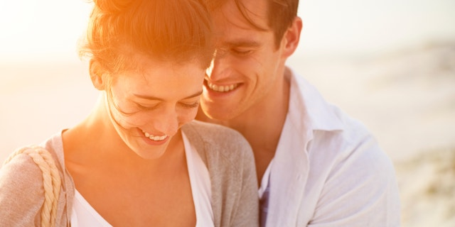beautiful young couple sharing intimate moment smiling on beach