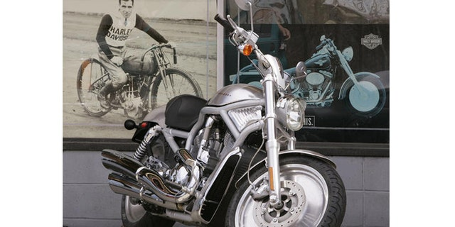 A new 2007 Harley Davidson V-rod motorcycle sits outside a dealership next to a poster of an early Harley Davidson V-twin racer in West Bridgewater, Mass., Thursday morning, April 19, 2007. Harley Davidson, Inc., a 104 year-old American motorcycle builder, announced Thursday its first quarter profits fell 18 percent. (AP Photo/Stephan Savoia)