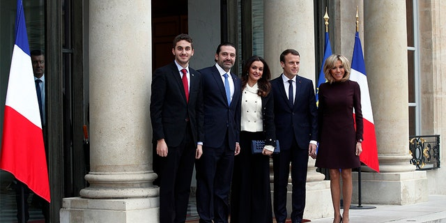 French President Emmanuel Macron and his wife Brigitte, right, greet Lebanon's Prime Minister Saad Hariri, second left, his wife Lara, center left, and their son Hussam upon their arrival at the Elysee Palace in Paris, Saturday.