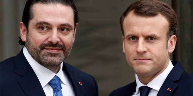 French President Emmanuel Macron, right, poses for photographers with Lebanon's Prime Minister Saad Hariri prior to their meeting at the Elysee Palace in Paris, Saturday