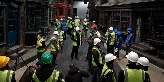"in this 2012 photo, press members and workers view ""Diagon Alley"" during a tour of the set of the Harry Potter films at the Warner Bros. Studios in Leavesden."