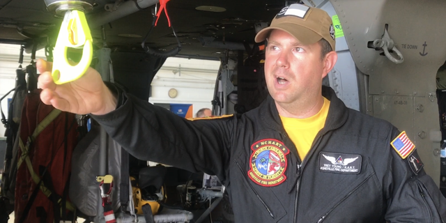 Asheville firefighter and HART helicopter search and rescue technician Trey Young explains how rescuers hoist a basket down to victims in air rescues.