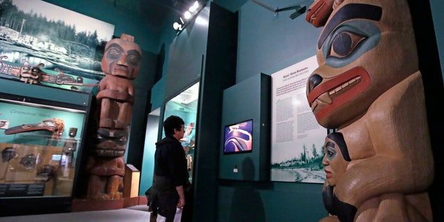 A visitor stands among totem poles as she watches a video as part of Hall of the North American Indian exhibit, at the Peabody Museum of Archaeology & Ethnology at Harvard University in Cambridge, Mass., Thursday, Oct. 13, 2016.