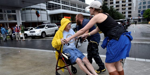 Aid workers push evacuee Frank Andrews into the George R. Brown Convention Center after Hurricane Harvey inundated the Texas Gulf coast with rain causing widespread flooding, in Houston, Texas, U.S. August 27, 2017. REUTERS/Nick Oxford