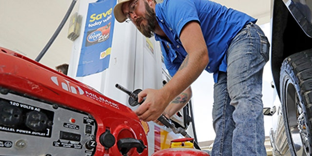 Aaron Berg fills up a gas can and his portable generator, Aug. 24, 2017.
