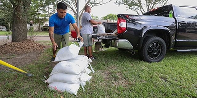 Albert Martinez and Victor Valerio fill bags with dirt from a pickup, Aug. 24, 2017