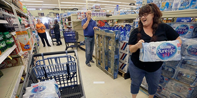 Kristy Ahrens of Galveston buys 4 cases of water at Kroger, 5730 Seawall Blvd., Aug. 24, 2017