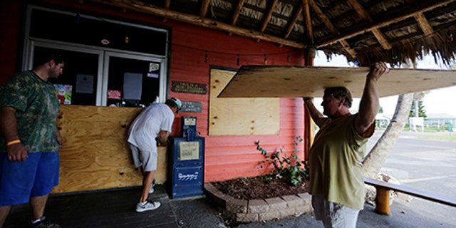 Mac Owens, left, Mark Jones, center, and Kelly Owens, right, board up their business in preparation for Hurricane Harvey, Aug. 24, 2017