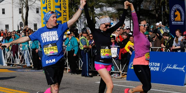 Bombing survivor and amputee Adrianne Haslet crossed the Boston Marathon finish line after more than 10 hours on the course. (photograph by Boston Globe/Getty Images)
