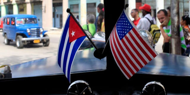 In this March 22, 2013 file photo, miniature flags representing Cuba and the U.S. are displayed on the dash of an American classic car in Havana, Cuba.