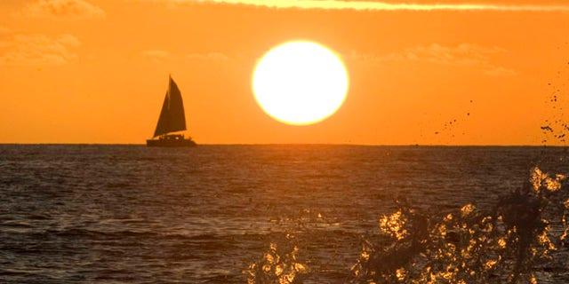 Waves crash into a wall as the sun sets on Waikiki Beach in Honolulu, Hawaii.