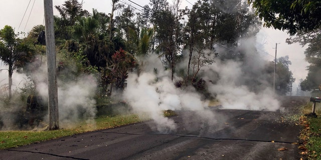This May 7, 2018, file photo from the U.S. Geological Survey shows gas and steam rising from multiple fissures on Moku Street in the Leilani Estates Subdivision near Pahoa on the island of Hawaii.