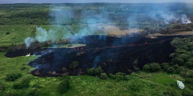 In this May 13, 2018 photo released by the U.S. Geological Survey, gases rise from a fissure near Pahoa, Hawaii.