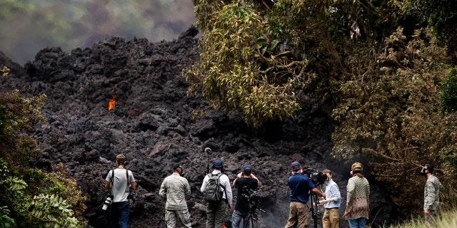 Members of the media record a wall of lava entering the ocean near Pahoa.