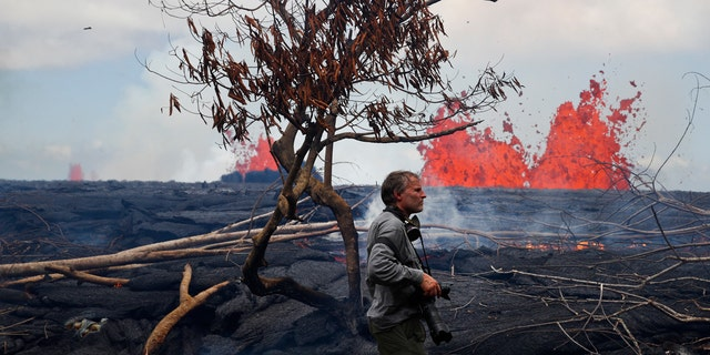 Photographer Carsten Peter, of Germany, watches lava erupt from fissures in the Leilani Estates subdivision near Pahoa, Hawaii, Tuesday, May 22, 2018.