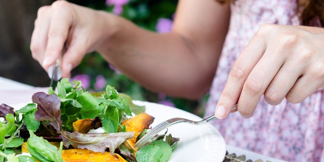 Pair of woman's hands holding cutlery eating a fresh healthy raw spring salad with butternut pumpkin squash at a casual outdoor dining meal location