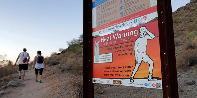 A sign warns hikers about severe heat as they begin their hike at sunrise to avoid the excessive heat, Friday, June 16, 2017, in Phoenix.