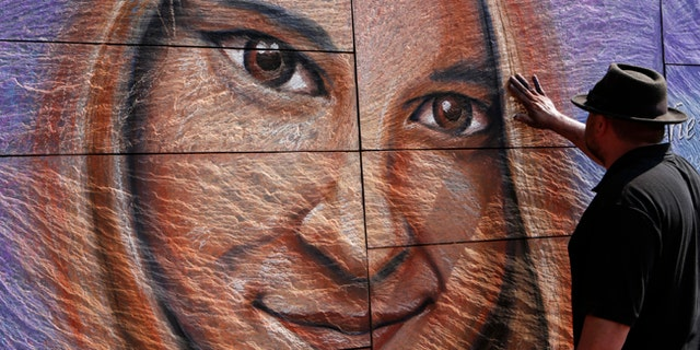Artist Sam Welty creates a chalk mural of Heather Heyer during her memorial service Wednesday, Aug. 16, 2017, in Charlottesville, Va. Heyer was killed Saturday, when a car rammed into a crowd of people protesting a white nationalist rally. (AP Photo/Julia Rendleman)