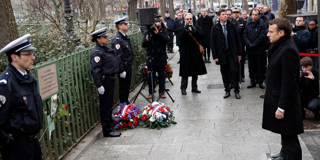 French President Emmanuel Macron observes a minute of silence in front of the plaque commemorating late police officer Ahmed Merabet to mark the third anniversary of the attack, in Paris, Sunday, Jan. 7, 2018.