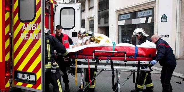 An injured person is transported to an ambulance after a shooting, at the French satirical newspaper Charlie Hebdo's office, in Paris, Wednesday, Jan. 7, 2015. Masked gunmen stormed the offices of a French satirical newspaper Wednesday, killing at least 11 people before escaping, police and a witness said. The weekly has previously drawn condemnation from Muslims. (AP Photo/Thibault Camus)