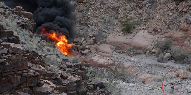 A survivor, lower right, walks away from the scene of a deadly tour helicopter crash along the jagged rocks of the Grand Canyon.