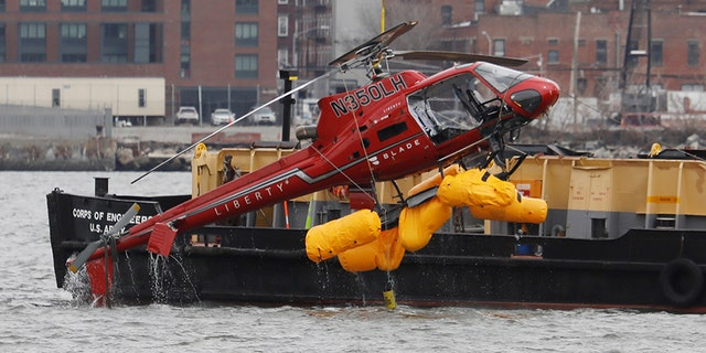The wreckage of a chartered Liberty Helicopters helicopter that crashed into the East River during a photo shoot tour is hoisted from the water in New York City.  (REUTERS/Shannon Stapleton)