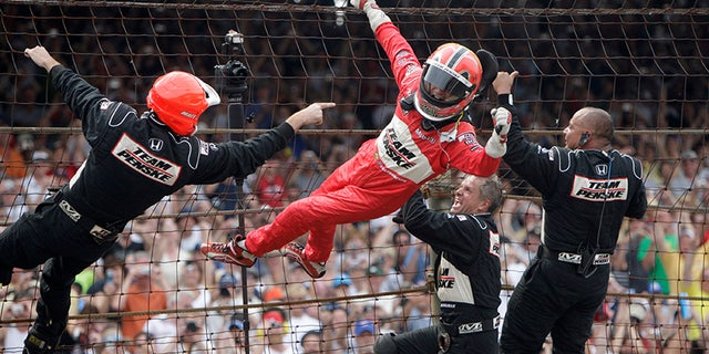 Castroneves climbs the catch fence at the Indianapolis Motor Speedway after his third Indy 500 win