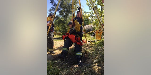 Rescuers being lowered into the drain on May 1.