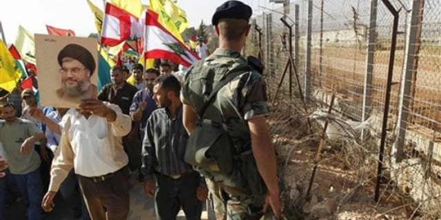 June 2: A Hezbollah supporter holds up a poster of Hezbollah leader Sheik Hassan Nasrallah as he protests with others along the Lebanese-Israeli border in southern Lebanon.