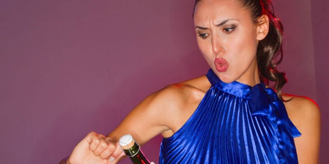 Young woman puckering lips as she struggles to open champagne bottle at nightclub. Horizontal shot
