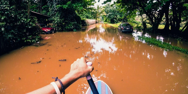 This Sunday, April 15, 2018, photo provided by Kauai resident James Hennessy shows the view as he maneuvers a stand-up paddleboarding along his flooded street in Haena, Hawaii.