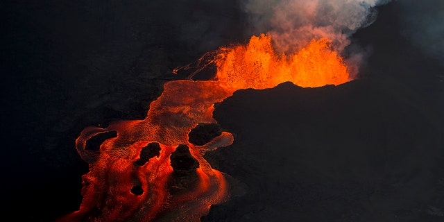 Lava from the Kilauea volcano continues to erupt from a fissure and forms a river of lava flowing down to Kapoho.