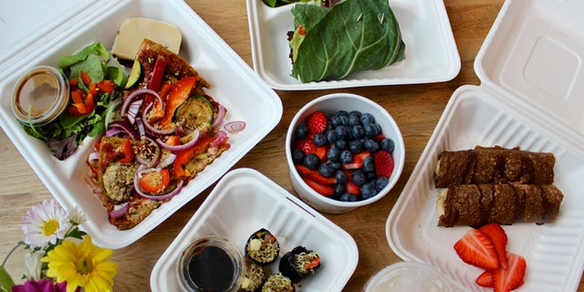 A day's worth of meals from a raw-vegan delivery service, ready for a cleanse or detox. Includes: crepes, berries, collard green wraps, sushi, salad and pizza.