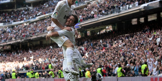 Real Madrid's Gonzalo Higuain from Argentina, bottom, reacts after scoring against Osasuna with Angel Di Maria from Argentina, right, during a Spanish La Liga soccer match at the Santiago Bernabeu stadium in Madrid, Sunday, Nov. 6, 2011. (AP Photo/Arturo Rodriguez)