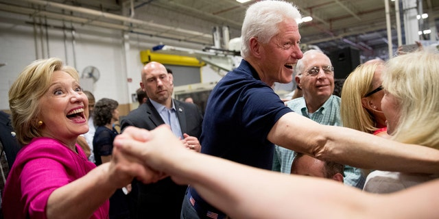 Hillary Clinton, far left, and Bill Clinton, right, shake hands with supporters.