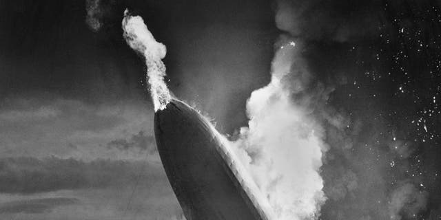 """FILE - In this May 6, 1937 file photo, the German dirigible Hindenburg crashes to earth in flames after exploding at the U.S. Naval Station in Lakehurst, N.J. Only one person is left of the 62 passengers and crew who survived when the Hindenburg burst into flames 80 years ago Saturday, May 6, 2017. Werner Doehner was 8 years old when he boarded the zeppelin with his parents and older siblings after their vacation to Germany in 1937. The 88-year-old now living in Parachute, Colo., tells The Associated Press that the airship pitched as it tried to land in New Jersey and that """"suddenly the air was on fire."""" (AP Photo/Murray Becker, File)"""