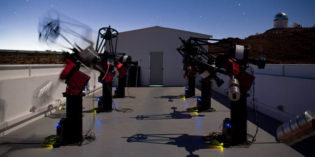 The MEarth-South telescope array, located on Cerro Tololo in Chile, searches for planets by monitoring the brightness of nearby, small stars. This long-exposure photograph shows MEarth-South telescopes observing at night; the blurred telescope is slewing from one star to another.