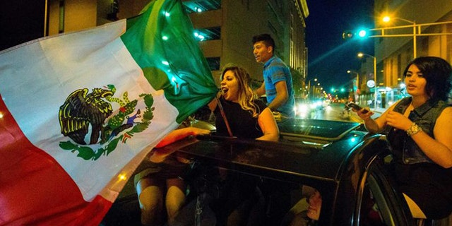 In this May 24, 2016, photo, a woman waves the Mexican flag while driving past the Albuquerque Convention Center after a rally by Republican presidential candidate Donald Trump in Albuquerque, N.M. Hispanic voters in Florida, New Mexico and California have waved Mexican flags and bashed Donald Trump piñatas to protest the Republican presidential contenders hard line approach to immigration.Yet far from the protests, an increasingly vocal Hispanic minority is speaking out in favor of the brash billionaire.  (Jett Loe/The Las Cruces Sun-News via AP) MANDATORY