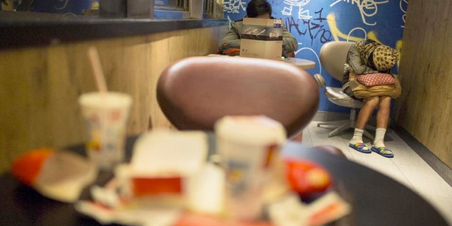 A woman sleeps with her belongings at night in a 24-hour McDonald's branch in Hong Kong.