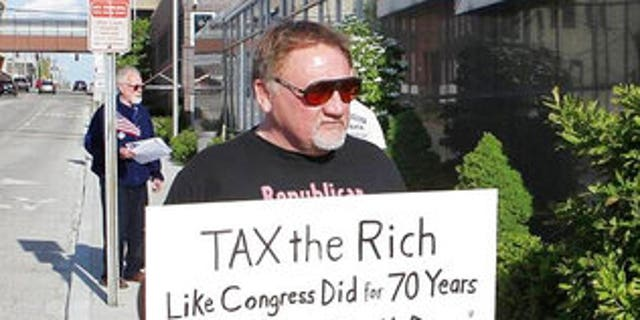 In this undated file photo, James Hodgkinson holds a sign during a protest outside of a United States Post Office in Belleville, Ill.