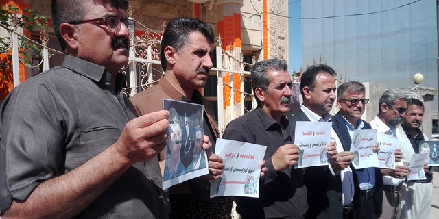 Survivors of the Halabja gas attacks hold pictures of relatives killed.