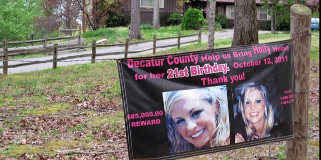 A poster with pictures of missing Tennessee nursing student Holly Bobo hanging on a fence in front of her house in Parsons, Tenn., in April 2013.
