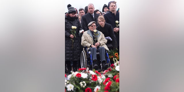 Former Nazi concentration camp survivor Raymond Renaud of France, center, holds a white rose during the wreath-laying ceremony on occasion of the international Holocaust remembrance day (Jan. 27) in the former Nazi concentration camp Buchenwald near Weimar, Germany, Friday.