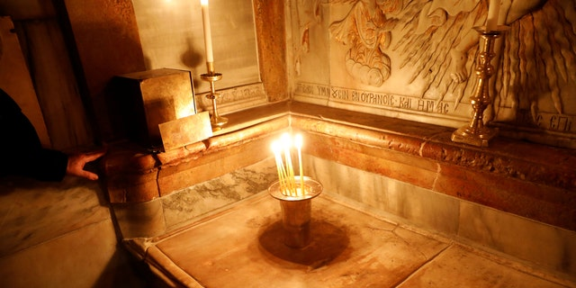 File photo - Candles are placed atop the newly restored tomb, which according to Christian belief is where Jesus's body was anointed and buried, inside the newly restored Edicule, the ancient structure housing the tomb, at the Church of the Holy Sepulchre in Jerusalem's Old City March 20, 2017. (REUTERS/Ronen Zvulun)