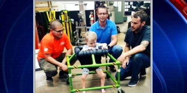 Silus Johnson, 2, tries out brand-new, custom-made walker built by some North Texas Home Depot employees. (Fox4 Dallas)