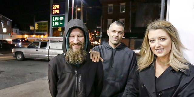 Johnny Bobbitt Jr., left, Kate McClure, right, and McClure's boyfriend Mark D'Amico pose at a CITGO station in Philadelphia. When McClure ran out of gas, Bobbitt, who is homeless, gave his last $20 to buy gas for her. McClure started a GoFundMe campaign for Bobbitt that raised hundreds of thousands of dollars.