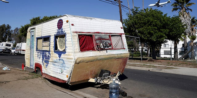 A plane flies over a homeless motor home and tent encampment near LAX airport in Los Angeles, California.